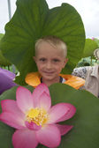 Cute little blond boy with lotus flower — Стоковое фото