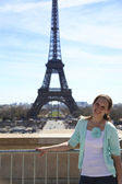 Young attractive woman near Eiffel Tower. Vacation in Paris. — Stock Photo