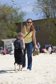 Mother and her little son walking on sand in sunny summer day — Stock Photo