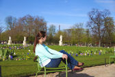 Brunette woman with long hair having rest in chair in Tuilleries — Stock Photo