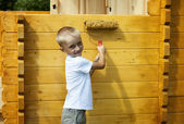 Cute little blond boy painting orange wall — Stock Photo