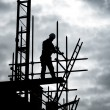 Foto Stock: Builder on scaffold building site