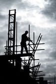 Builder on scaffold building site — ストック写真