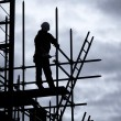 Builder on scaffold building site — Stock Photo #19994169