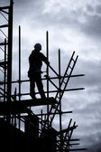 Builder on scaffold building site — Stockfoto