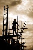 Builder on scaffold building site — Stock Photo