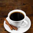 Cup of coffee with cinnamon sticks — Stock Photo