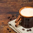Brown cup of coffee with cinnamon sticks — Stock Photo
