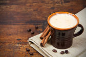 Brown cup of coffee with cinnamon sticks — 图库照片