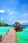 Zee met pier onder blauw bewolkte hemel — Stockfoto