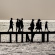 Silhouette of Family crossing bridge — Stock Photo