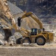 Stock Photo: Excavator shovel digging in gravel pit