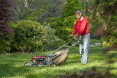 Senior man mowing his lawn — Stock Photo