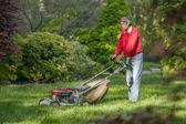 Senior man mowing his lawn — Stock Photo