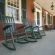 Rocking chairs on historic New England house - Stock Photo