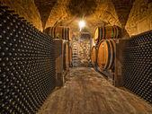 Wine bottles and oak barrels in cellar — Stock Photo