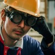 Hard working man in helmet - Stock Photo