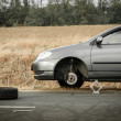 Car without tire on the road — Stock Photo