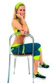 Junge fitnesstrainerin auf stuhl sitzend — Stockfoto