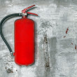Stock Photo: Red fire extinguisher on concrete wall