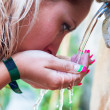 Thirsty girl drinking from outdoor tap — Foto Stock