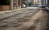Damaged car road with a lot of cracks — Stock Photo