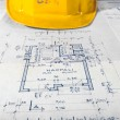 Yellow helmet of an engineer with plans — Stock Photo #32261129