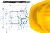 Yellow helmet of an engineer with plans — Stock Photo