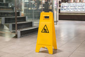 Yellow sign alerts for wet floor — Stock Photo