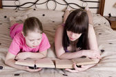 Girls reading book on bed — Stock Photo