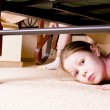 The child hides under a bed. — Stock Photo