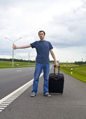 The young man pending on road with a suitcase — Stock Photo