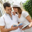 Couple of tourists using guide and tablet in town — Stock Photo #13935525