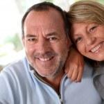 Portrait of happy senior couple sitting in sofa — Stock Photo #13939725