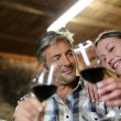 Couple of winemakers tasting red wine — Stock Photo #13930369