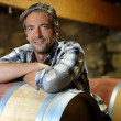 Stock Photo: Smiling winemaker leaning on wine barrel in winery