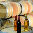 Closeup of bottles of wine set on barrel - Stock Photo
