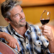 Winemaker looking at red wine in glass — Stock Photo #13930450