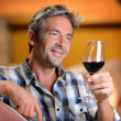 Winemaker looking at red wine in glass — Stock Photo