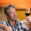 Winemaker looking at red wine in glass — Stock Photo #13930452