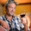 Winemaker looking at red wine in glass — Stock Photo #13930453