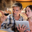 Winemakers in cellar using electronic tablet to control wine quality — Stock Photo