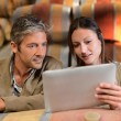Winemakers in cellar controlling wine market prices on tablet — Stock Photo #13930503