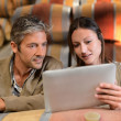 Winemakers in cellar controlling wine market prices on tablet - Stock Photo
