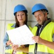 Construction team looking at blueprint — Stock Photo