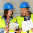 Construction team standing against building wall with blueprint — Stock Photo