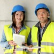 Construction team standing against building wall with blueprint — Stock Photo #13930584