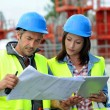 Engineers on building site controlling project — Stock Photo #13930616