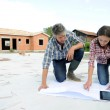 Couple checking construction plan on site — Stock Photo