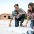Couple checking construction plon site — Stock Photo #13930658